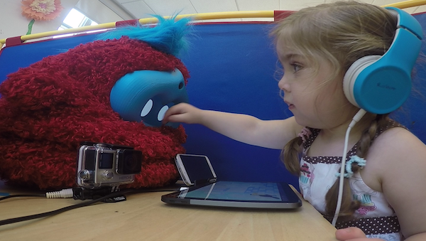 a girl reaches her hand toward the face of a fluffy red robot, which sits on the table in front of her