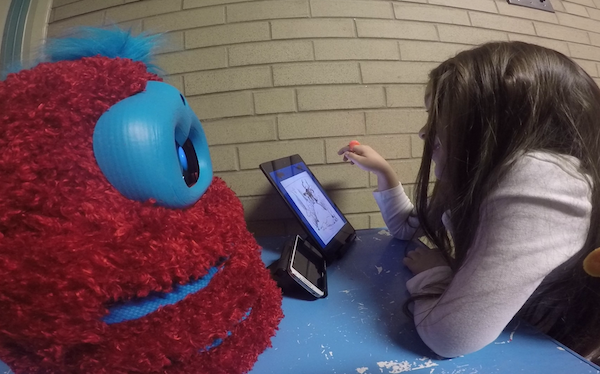 child leans over tablet showing a storybook, in front of a fluffy robot who is listening