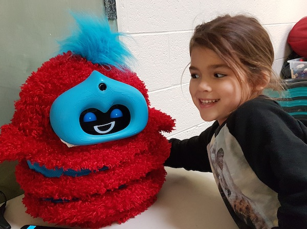 A girl grins at a red and blue fluffy robot and puts her arm around it