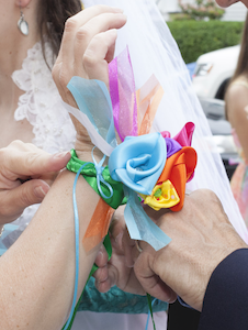 satin ribbon flower corsage being tied on to a woman's wrist