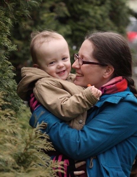 me hugging little Elian in front of evergreens