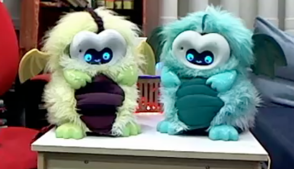 a pair of bright, fluffy dragon robots sitting beside each other on a table