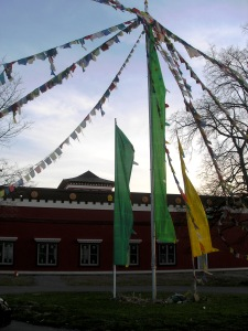 _Strings of prayer flags stretch out from the top of a pole in front of the temple with a sunset sky behind them_