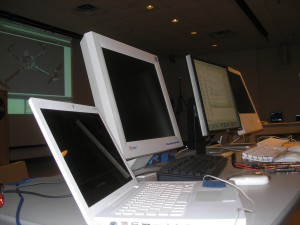 _four computers in a row on a table_