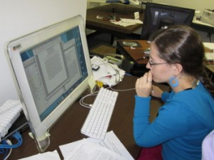 girl in blue sweater sitting at a computer with documents open