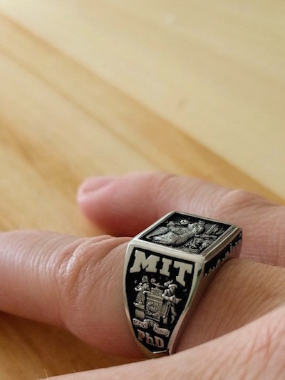 close up of a hand wearing a silver and black MIT ring