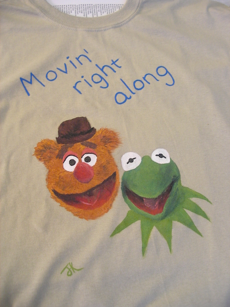 close up of t-shirt with text movin' right along and painted pictures of fozzie bear and kermit the frog
