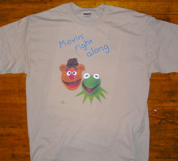 t-shirt with text movin' right along and painted pictures of fozzie bear and kermit the frog