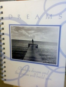 "spiral bound periwinkle-blue notebook, photo on the front and the words ""DREAMS: Build a dream and the dream will build you"""