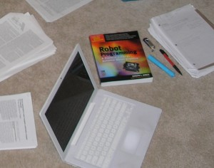 white laptop with printed papers and books