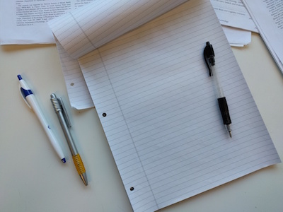 a pen sitting on a pad of paper with two extra pens beside it