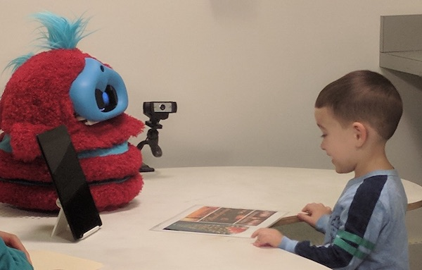a boy sits across a table from a red and blue robot