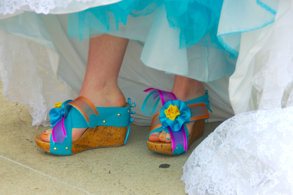cork wedge sandals with thick turquoise straps and ribbon flowers attached over the toes