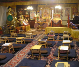 _the shrine room in the temple: five rows of cushions on the carpet leading up to altars and statues at the front of the room_