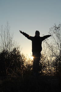 silhouette of person standing with arms raised in front of setting sun