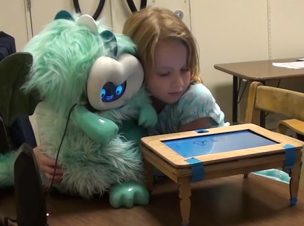 a young girl hugging a fluffy dragon robot behind a little play table