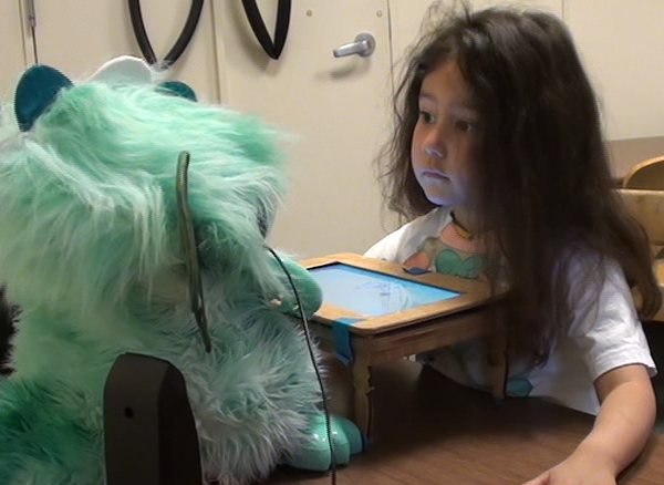 a girl looks at the dragonbot robot as it tells a story