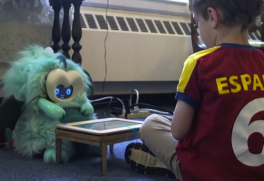 Boy sitting on the floor across a mini table from a dragon robot, looking at the robot intently