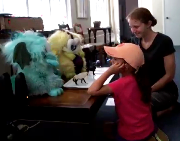 A child and a woman sit in front of a small table, looking at and talking with two fluffy dragon robots that are on the table