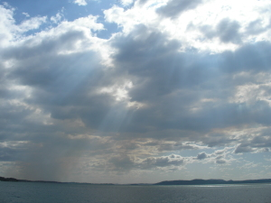 _sun beams through an array of puffy clouds over a grey-blue ocean_