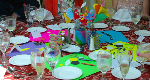 colorful sheets of scrapbook paper arranged in a circle on a table, with several jars in the middle containing a candle and paper flowers, with scrapbook materials scattered around