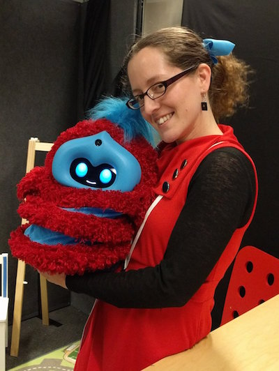a woman in a red dress holding tega, a fluffy red and blue robot