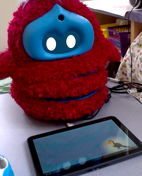 A fluffy red robot sits behind a tablet, which is laying on a table
