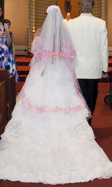 back of a woman wearing a white wedding dress with a veil draped down her back