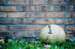 _volleyball sitting in grass beside a brick wall_